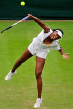 Venus Williams serves the ball in her 2011 Wimbledon Eleven outfit.JPG