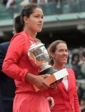 Ana Ivanovic holds the French Open trophy with Justine Henin looking on.jpg