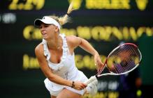 Caroline Wozniacki follows through on her serve during 2011 Wimbledon.JPG