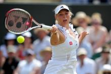 Caroline Wozniacki forehand on a high ball during 2011 Wimbledon.JPG
