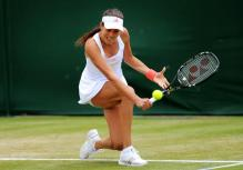 Ana Ivanovic goes down low to hit a 2 handed slice during 2011 Wimbledon.JPG