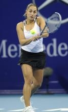 Tamira Paszek two handed backhand in a white tanktop and black skirt.JPG