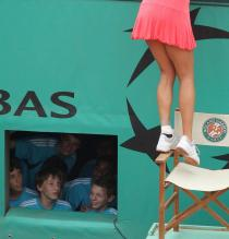 Ana Ivanovic tries to stand on a chair to reach the stands.jpg
