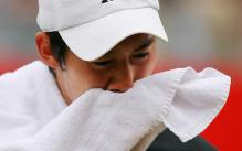 Kei Nishikori wipes his face with a towel.jpg