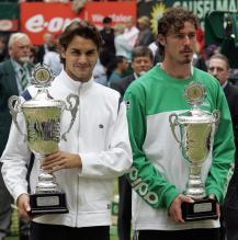 Roger Federer and Marat Safin hold their trophies.jpg