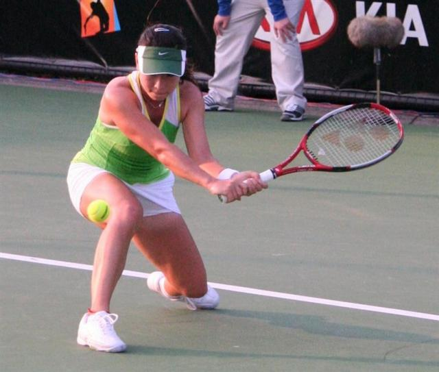 Zheng Jie gets low for a two-handed slice.jpg
