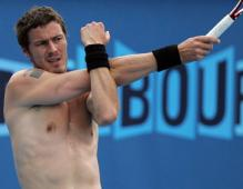 Marat Safin stretches his arm without a shirt on.jpg