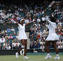 Venus Williams and Serena are happy after winning the 2008 Wimbledon doubles finals.jpg