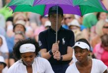 Venus and Serena Williams rest as an attendant intently holds an umbrella to cover them.jpg