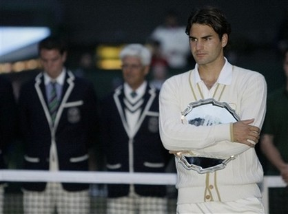 Roger Federer looks on holding his runner up trophy.jpg