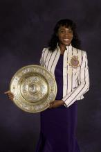 Venus Williams in a purple dress holding her 2008 Wimbledon trophy in this formal photo.jpg