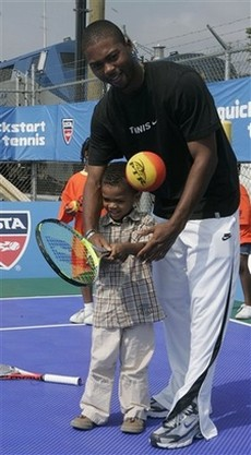 Donald Young helps a 3 year old tennis prodigy.jpg