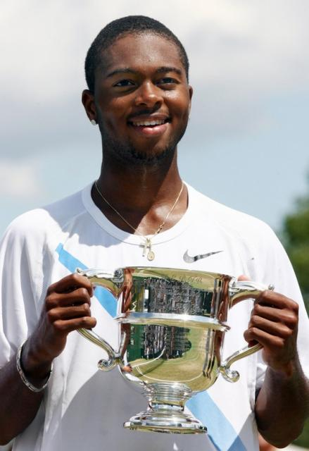Donald Young holds up a silver trophy cup.jpg