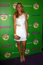 Nicole Vaidisova in a short white dress with a gold wallet.jpg