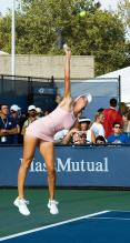 Nicole Vaidisova in short pink tennis dress leaps up to hit a serve.jpg