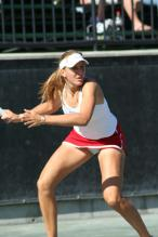 Nicole Vaidisova in a short red tennis skirt gears up to hit a forehand.jpg
