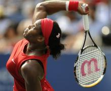 Serena Williams goes after the ball on her service motion.jpg