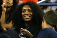 Venus Williams smiles as she watches Serena play the 2008 US Open finals.jpg