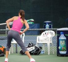 Jelena Jankovic stretching in gray warm up pants.jpg