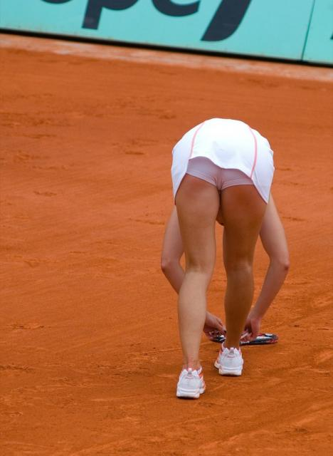 Jelena Jankovic bends over and checks her racquet.jpg