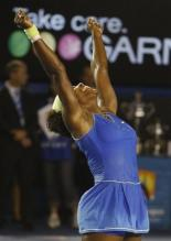 Serena Williams is elated and raises her arms in celebration.jpg