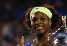 Serena Williams raises her finger and stands next to her Aussie Open 2009 Trophy.jpg