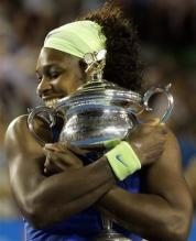 Serena Williams clasps her Australian Open 2009 trophy to her chest.jpg