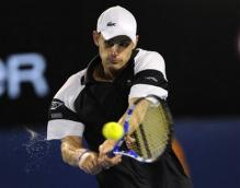 Andy Roddick hits a two-handed backhand as his sweat beads fly.jpg