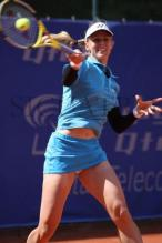 Elena Dementieva in blue skirt hits a high forehand.jpg