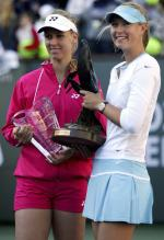 Elena Dementieva in pink jacket and shorts stands next to Maria Sharapova.jpg
