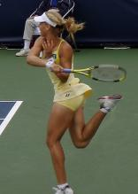 Elena Dementieva in tight yellow shorts shows her forehand follow through.jpg