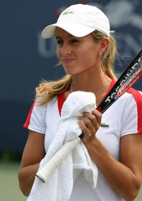 Gisela Dulko smiles while holding a towel and her Tecnifiber racquet.jpg