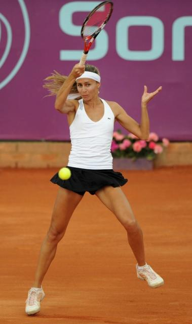 Gisela Dulko hits a forehand in white tanktop and short black skirt.jpg